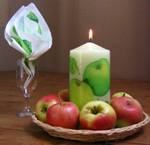 Centerpiece with apple decoupage pillar candle in the middle, surrounded by fresh apples