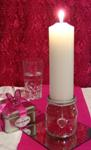 Glass jar candle holder filled with pink beads, holding white, pointed pillar candle