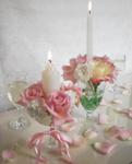rose and carnation arrangements in wine glasses with ivory candles