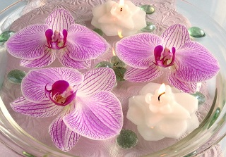 Floating orchid flowers and candles