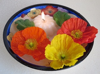 Floating poppy flowers and candle