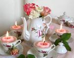 centerpiece with pink floating candles in teacups, roses and carnations in teapot