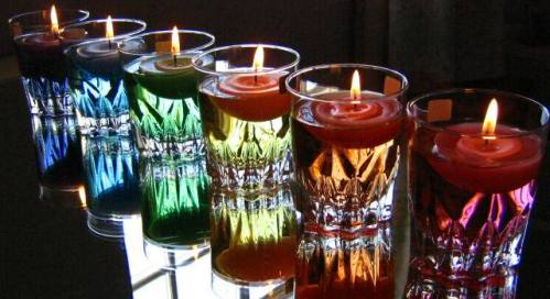 brandy glasses with colored water and floating candles