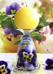 Pansy arrangement in upside down wineglass, with yellow ball candle on top