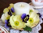 Poppy and pansy arrangement with large ivory, cylinder candle in the middle