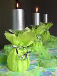 Wine glasses decorated with lime napkins and silver ribbons